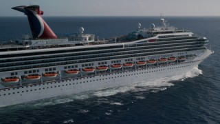 AX103_074 - 5k stock footage aerial video of a Carnival cruise ship in Caribbean blue waters, St Thomas