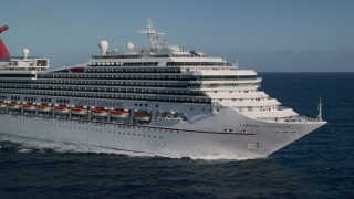 AX103_075 - 5K stock footage aerial video of a Carnival cruise ship in Caribbean blue waters off the coast, St Thomas