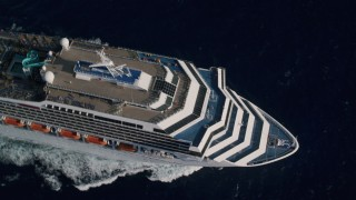 AX103_077 - 5k stock footage aerial video of Carnival cruise ship pool area on Caribbean blue waters, St Thomas