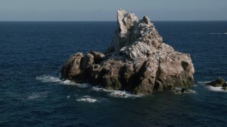 AX103_082 - 5k stock footage aerial video of a Rock formation in Caribbean blue waters, St Thomas