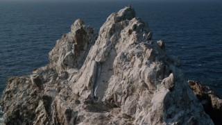 AX103_084 - 5k stock footage aerial video of a Jagged rock formation in Caribbean blue waters, St Thomas