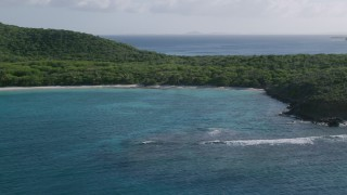 AX103_091 - 5k stock footage aerial video of Caribbean beach and jungle along turquoise waters, Culebrita, Puerto Rico