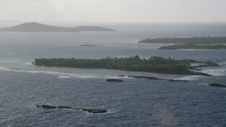 AX103_113 - 5k stock footage aerial video of a Small Caribbean island with vegetation and a home, Puerto Rico