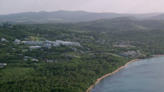 AX103_117 - 5k stock footage aerial video of Condominiums nestled in trees with views of Caribbean blue waters, Fajardo, Puerto Rico