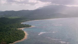 AX103_118 - 5k stock footage aerial video of a Caribbean beach and jungle along turquoise blue waters, Fajardo, Puerto Rico