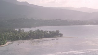 AX103_122 - 5k stock footage aerial video of Palm trees and beach along Caribbean blue waters, Luquillo, Puerto Rico