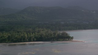 AX103_123 - 5k stock footage aerial video of Palm trees and beach along turquoise blue Caribbean waters, Luquillo, Puerto Rico
