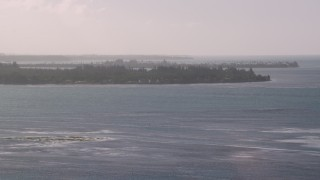 AX103_125 - 5k stock footage aerial video Approaching an island in blue Caribbean waters, Rio Grande, Puerto Rico