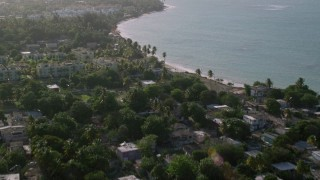 AX103_132 - 5k stock footage aerial video of Palm trees, beach front homes along Caribbean blue waters, Loiza, Puerto Rico