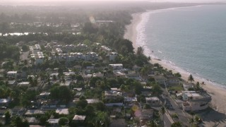 AX103_133 - 5k stock footage aerial video of Beachfront homes and Caribbean beach along blue waters, Loiza, Puerto Rico