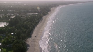 AX103_134 - 5k stock footage aerial video of Caribbean beach along turquoise waters, Loiza, Puerto Rico