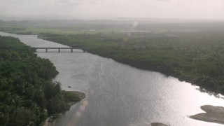 AX103_136 - 5K stock footage aerial video of a Bridge over a river surrounded by vegetation, Loiza, Puerto Rico
