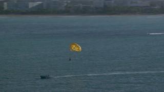 AX103_146 - 5k stock footage aerial video Parasailing in Caribbean blue waters, San Juan, Puerto Rico