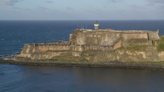 AX104_007 - 5k stock footage aerial video of Fort San Felipe del Morro along Caribbean blue waters, Old San Juan, sunset