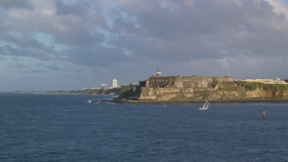 AX104_013 - 5k stock footage aerial video of Fort San Felipe del Morro along Caribbean blue waters, Old San Juan, sunset