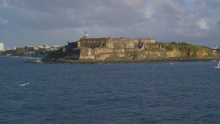 AX104_014 - 5k stock footage aerial video of Fort San Felipe del Morro along blue ocean waters, Old San Juan, sunset