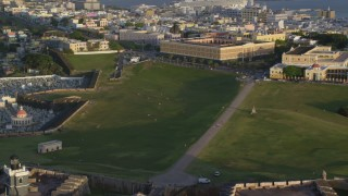AX104_018 - 5k stock footage aerial video of Cementerio Santa María Magdalena de Pazzis, Fort San Felipe del Morro, Old San Juan, sunset