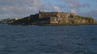 AX104_020 - 5k stock footage aerial video of Fort San Felipe del Morro and lighthouse, Old San Juan, sunset