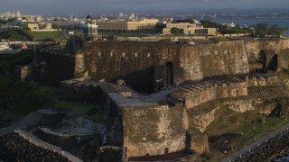 AX104_021 - 5k stock footage aerial video of Fort San Felipe del Morro and lighthouse, Old San Juan, sunset