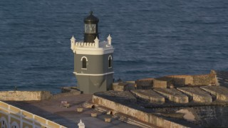 AX104_022 - 5k stock footage aerial video of Port San Juan Light, Fort San Felipe del Morro, Old San Juan, sunset