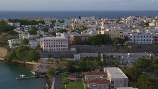 AX104_037 - 5k stock footage aerial video of La Fortaleza and neighboring buildings, Old San Juan sunset