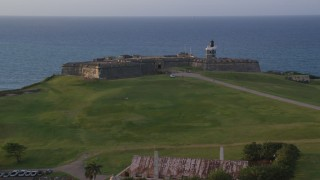 AX104_042 - 5k stock footage aerial video of Fort San Felipe del Morro overlooking the ocean, Old San Juan sunset