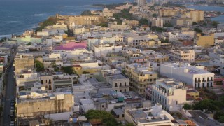 AX104_043 - 5k stock footage aerial video Caribbean buildings and Fort San Cristobal, Old San Juan sunset