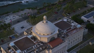 AX104_048 - 5k stock footage aerial video of San Juan Capitol Building looking out on the ocean, Old San Juan Puerto Rico, sunset