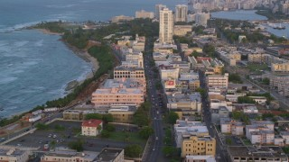 AX104_053 - 5k stock footage aerial video Following Avenida Juan Ponce de Leon through buildings, Old San Juan, Puerto Rico, sunset