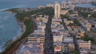 AX104_054 - 5k stock footage aerial video of Avenida Juan Ponce de Leon through buildings, Old San Juan, Puerto Rico, sunset