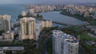 AX104_058 - 5k stock footage aerial video of Avenida Ashford bridge and high-rises, San Juan, Puerto Rico, sunset