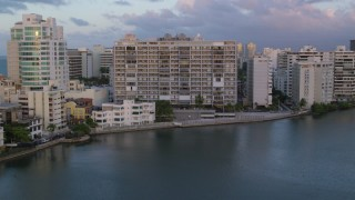 AX104_061 - 5K stock footage aerial video of Hotels along Caribbean blue waters, San Juan, Puerto Rico sunset