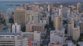 AX104_062 - 5k stock footage aerial video of Oceanside Caribbean hotels and apartment buildings, San Juan, Puerto Rico sunset