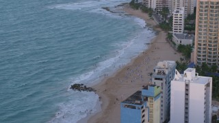 AX104_063 - 5k stock footage aerial video of a Caribbean beach and turquoise waters, San Juan, Puerto Rico, sunset
