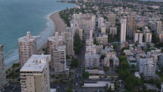 AX104_065 - 5k stock footage aerial video of Beachfront hotels and Caribbean blue waters, San Juan, Puerto Rico, sunset