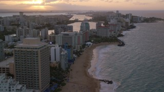 AX104_069 - 5k stock footage aerial video of Beachfront Caribbean hotels along the ocean, San Juan, Puerto Rico, sunset