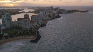 AX104_070 - 5k stock footage aerial video of Beachfront Caribbean hotels along the ocean, San Juan, Puerto Rico, sunset