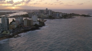 AX104_071 - 5k stock footage aerial video of the Oceanfront Caribe Hilton Hotel, San Juan, sunset