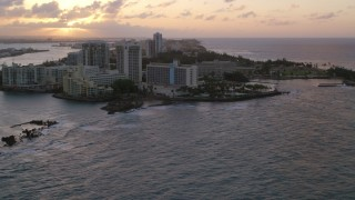 AX104_072 - 5k stock footage aerial video of the Oceanfront Caribe Hilton Hotel, Normandie Hotel, San Juan, Puerto Rico, sunset