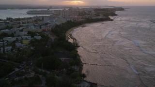 AX104_075 - 5K stock footage aerial video of Caribbean buildings near the beach and ocean, Old San Juan, Puerto Rico, sunset