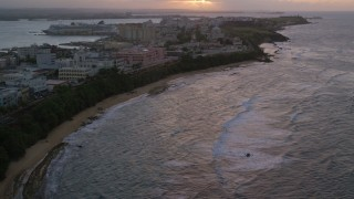 AX104_076 - 5k stock footage aerial video Approaching San Juan Capitol Building along the coast, Puerto Rico, sunset