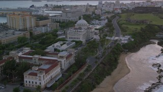 AX104_077 - 5k stock footage aerial video of San Juan Capitol Building along the coast, Puerto Rico, sunset