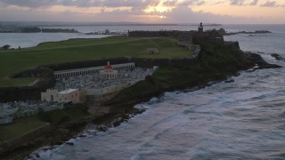 AX104_080 - 5k stock footage aerial video Approaching Fort San Felipe del Morro and lighthouse, Old San Juan, sunset