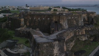 AX104_083 - 5k stock footage aerial video of Fort San Felipe del Morro, Old San Juan, twilight