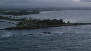 AX104_092 - 5k stock footage aerial video of Isla de Cabras and waves along the coast, San Juan, twilight