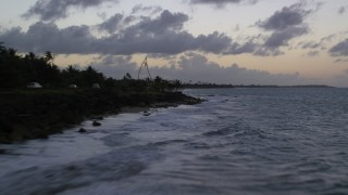 AX104_100 - 5k stock footage aerial video Flying over Caribbean waters along a highway and beach with palm trees, Dorado, Puerto Rico, twilight