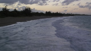 AX104_104 - 5k stock footage aerial video of Caribbean blue waters along a beach, Dorado, Puerto Rico, twilight