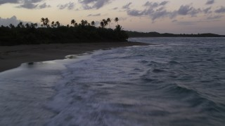 AX104_105 - 5k stock footage aerial video Flying low along a Caribbean beach and ocean waters, Dorado, Puerto Rico, twilight