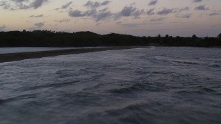 AX104_106 - 5k stock footage aerial video Flying over the ocean toward oceanfront homes on the coast, Dorado, Puerto Rico, twilight