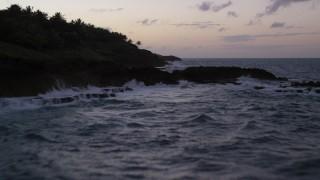 AX104_118 - 5k stock footage aerial video of the Rugged Caribbean coast along the ocean, Dorado, Puerto Rico, twilight